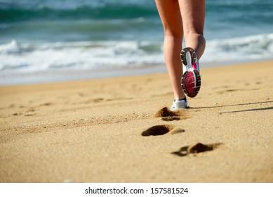 Woman running on beach. Sport footwear, sand footprints and legs close up. Runner feet detail.