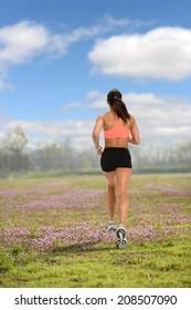 Woman running on beautiful field of flowers