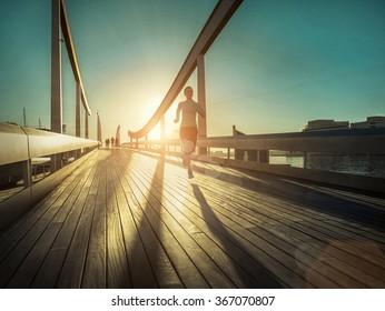 Woman running on the bridge under sunlight.