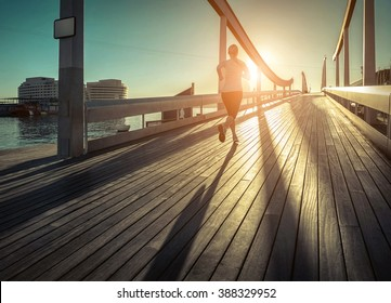 Woman running on the bridge under sunlight.