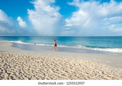 Woman Running on a Caribbean Beach Early in the Morning