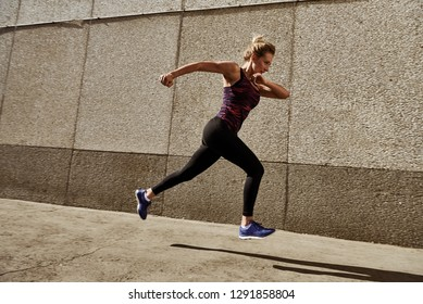 Woman running on the city street against modern city walls.