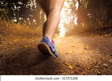 woman running on a dirt trail during the sunset or sunrise with a toned instagram retro filter