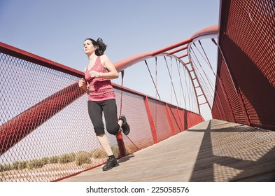 woman running on a footbridge to sunny day