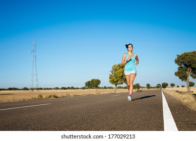 Woman running on road. Female sweaty athlete exercising.