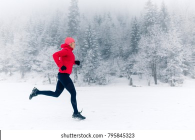 Woman running on snow in winter mountains. Sport, fitness inspiration and motivation. Young happy woman trail running in mountains on snow, winter day. Female trail runner jogging outdoors.