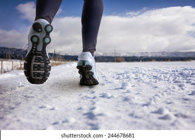 woman running on a snowy country road with view of the snow covered mountains in background on a sunny afternoon