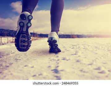 woman running on a snowy country road with view of the snow covered mountains in background with instagram filter (shallow depth of field)
