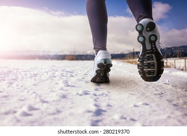 woman running on a snowy country road with view of the snow covered mountains on an afternoon day with sun flare (shallow depth of field)