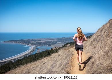 Woman running on a trail high above Stinson Beach, CA.