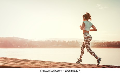 Woman running outdoors on sunny day by the water