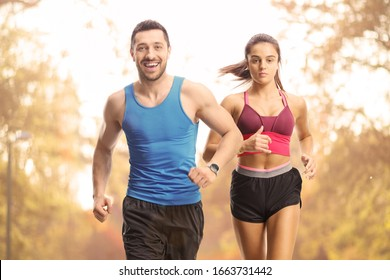 Мan and woman running outdoors on a sunset in a park