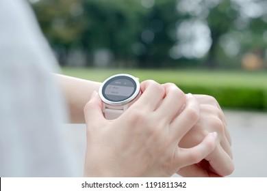 Woman running outdoors using watch