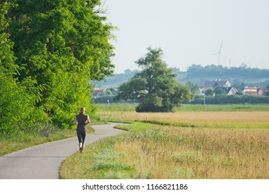 Woman running seen from behind on a paved road through meadows and beside trees of the National Park Neusiedlersee in Burgenland with the village of Weiden am See in the background.
