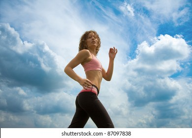 Woman running with a sky backdrop