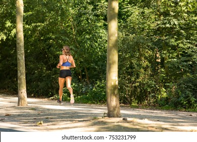 Woman running in a sunny Amsterdam Vondelpark in the Netherlands.