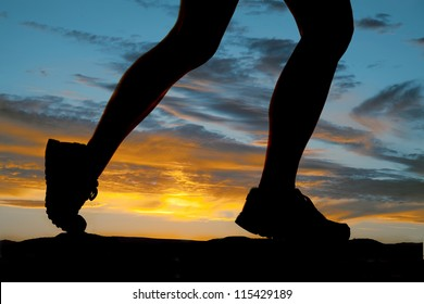 A woman running in the sunset legs silhouette.