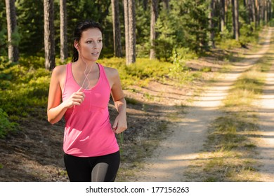 Woman running through forest outdoor training on sunny day