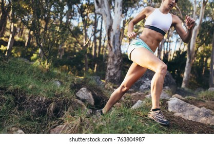 Woman running through rocks and hard surface. Athletic woman running on a rough terrain in a forest.