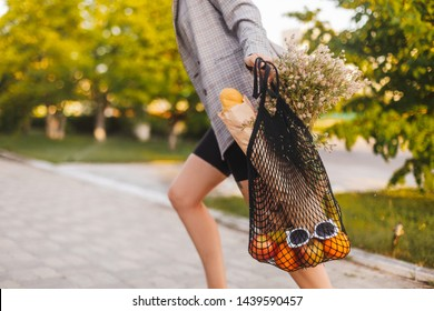 Woman running with tote bag. Girl in a hurry run at home. Black grid eco bag with sunglasses, fruits orange, lemons, bananas, bread in craft paper bag and wildflowers. Bussines woman is late at home.