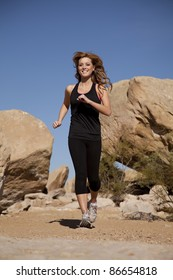 A woman running towards the camera with a smile on her face in the outdoors.