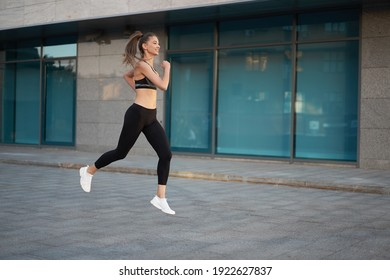 Woman running urban city street background Active sporty caucasian female morning workout Healthy lifestyle concept. Athletic person dressed sportswear do exercises  Corporate building windows