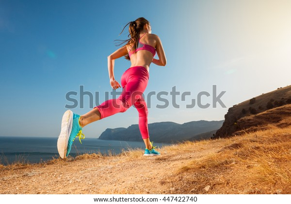 Woman running. Young girl runner jogging on a mountain trail in the beautiful landscape. Healthy sport lifestyle. Fitness and workout on outdoors.