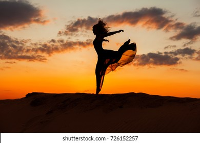 Woman runs along the barkhans against the backdrop of the setting sun.