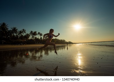Woman runs barefoot on the beach at sunset. Silhouette of a woman by the sea at sunrise