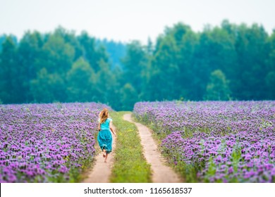 Woman runs in the field with purple flowers
