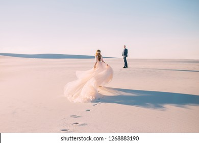 A woman runs to meet a man. Dress with a very long hairpin that flies in the wind. Photo from the back without a face. Background desert at sunset. Fine art photo