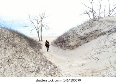 Woman runs on beach trail on a cold Spring day in Sandbanks Provincial Park, Ontario, Canada