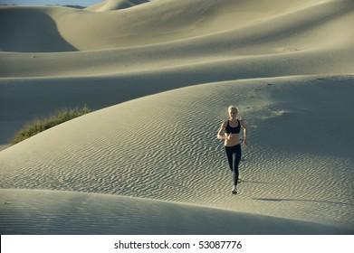 Woman runs on sand dunes.