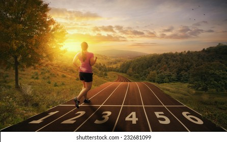 A woman runs on a track through the valley. - Shutterstock ID 232681099