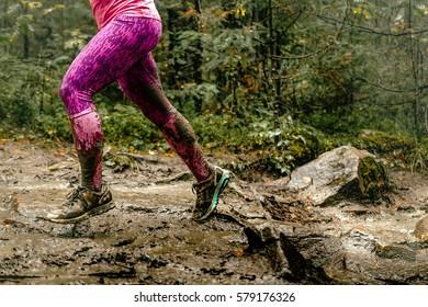 woman runs over rocks in forest legs in spray dirt