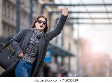 Woman in rush at the city street calling taxi, urban scene
