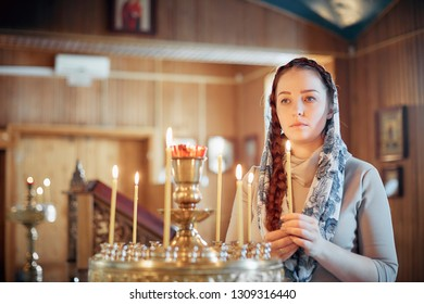 woman in the Russian Orthodox Church with red hair and a scarf on her head lights a candle and prays in front of the icon.