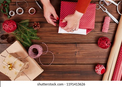 Woman s hands wrapping Christmas gift, close up. Unprepared christmas presents on wooden background with decor elements and items, top view. Christmas or New year DIY packing Concept.