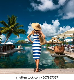 Woman in sailor striped dress near poolside jetty at Seychelles