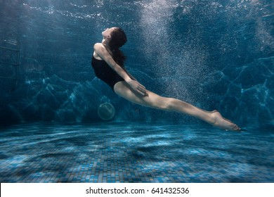Woman sails at the bottom of the pool, she dives under the water.