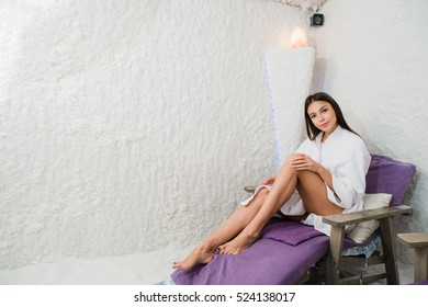 Woman in salt room. Beautiful young girl in bathrobe relaxing in spa
