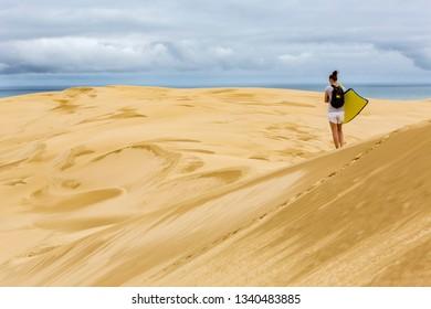 Woman with sandboard Giant sand dunes, Te Paki, Northland, North Island, New Zealand