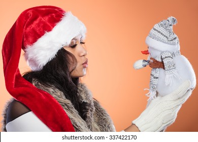 Woman in santa claus hat holding little snowman. Mixed race african girl. Christmas.