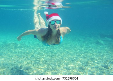 Woman in Santa Claus hat swimming underwater in sea, Christmas vacation at sea concept