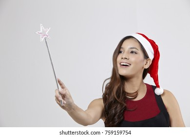 woman with santa hat holding a magic wand
