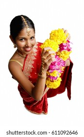 Woman in sari, holding flower garland, high angle view