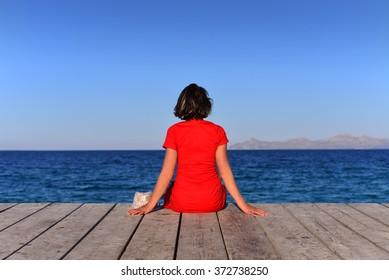 Woman sat on jetty at Majorca, Balearic Islands, Spain.