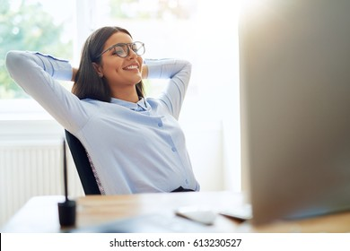 Woman with satisfied expression at desk. Arms up and folded behind her head in front of bright window.