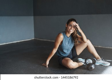 Woman satisfied gasping productive workout training session, Attractive sportswoman wipe sweat off forehead smiling pleased, rest sit gym floor, finish workout training session, train kettlebell