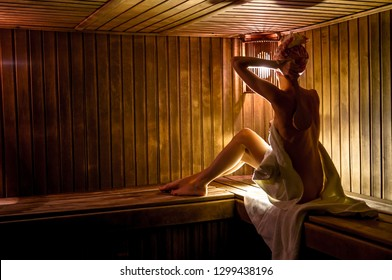 Woman in a  sauna with a brush for skin massage wrapped in a white towel